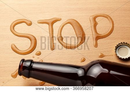 Beer Bottle And Spilled Beer In The Shape Of The Word Stop. Ban Alcohol