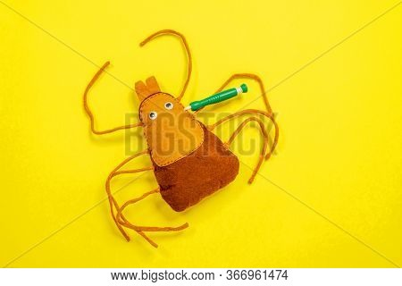 The Mite Sift Toy With Sticking Syringe Lying On Bright Yellow Background. Concept Of Seasons Or Pla