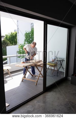 Worker In Home Clothes Screwing Wooden Parts Together. Senior Grey-haired Man Working At Balcony Wit