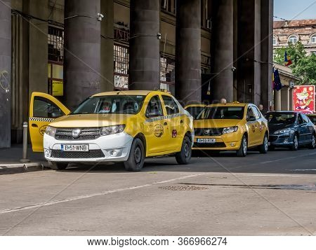 Bucharest/Romania - 05.16.2020: Taxi cars waiting in line for clients in front of the North Railway Station (Gara de Nord). The taxi drivers are famous for scamming tourist that have just arrived