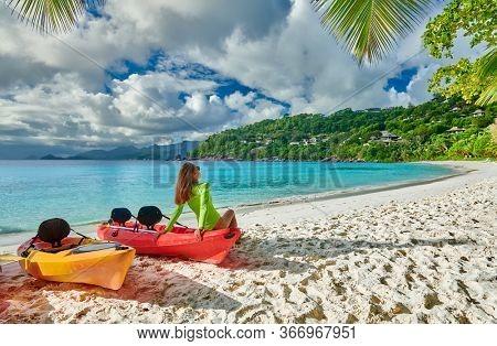 Woman sitting on kayak. Beautiful Petite Anse beach with palm tree at Seychelles, Mahe