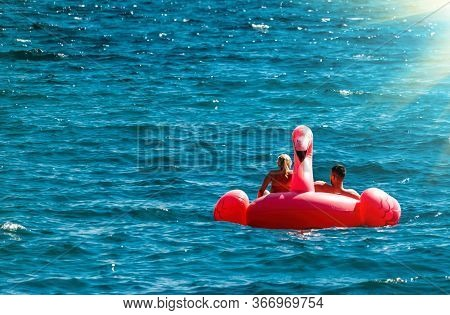 Couple Having Fun On Pink Flamingos At Blue Sea. Sunset Holiday Travel Vacation Background With Funn
