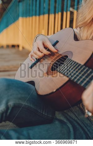 Learning To Play The Guitar. Beginner Guitar Lesson. Close-up Of Female Hand Playing Acoustic Guitar