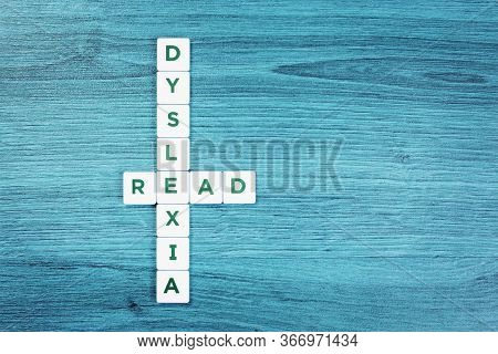 Dyslexia And Read Word Cubes On Blue Wooden Desk Background, Reading Difficulty Awareness And Disord