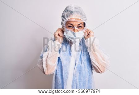 Middle age nurse woman wearing protection coronavirus equipment over white background covering ears with fingers with annoyed expression for the noise of loud music. Deaf concept.