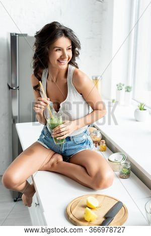 Beautiful Smiling Girl Holding Glass Of Smoothie Near Pieces Of Lemon On Cutting Board On Kitchen Wo