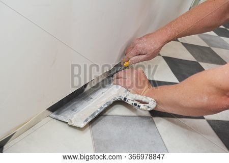 A Building Contractor Is Installing A Linoleum, Vinyl Flooring And Cutting Off, Trimming The  Outsid