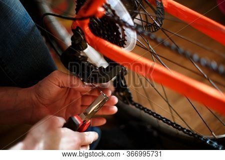 Hand Of A Man With A Multitool Near The Wheel And Brakes Of The Bike. Bike Repair, Setting Up Disc B