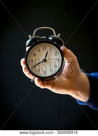 Black vintage alarm clock in a man's hand