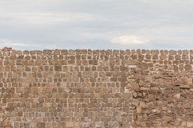 Old Stable Stone Wall With Rows Of Crafted Masonry Stones. Brickwork With Individual Craft Bricks Pa