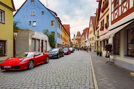 Rothenburg Ob Der Tauber, Germany - September 24, 2014: View On City Street With Red Ferrari And Oth