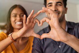 Close up of middle eastern couple making heart shape with hands. Beautiful young indian couple in love making heart sign with hands. Portrait of two happy smiling lovers at home.