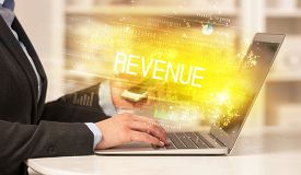 Closeup of businessman hands working on laptop with REVENUE inscription, succesfull business concept