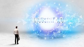 Rear view of a businessman standing in front of INDUSTRY 4.0 inscription, modern technology concept