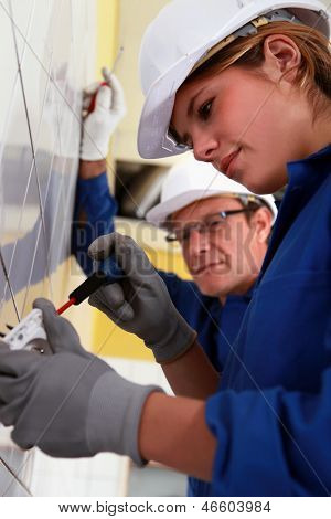 Young woman installing an electrical outlet