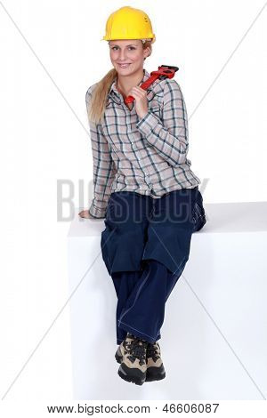 Tradeswoman sitting on a block and holding a pipe wrench