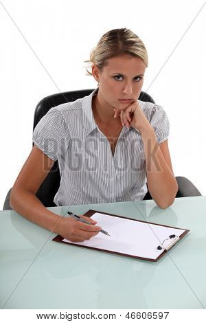 Standoffish woman writing on a clipboard