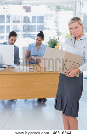 Forlorn businesswoman leaving office after being let go carrying box of things