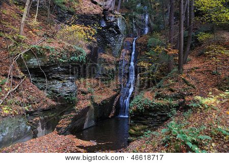 Autumn Waterfall in mountain with foliage and woods over rocks. Silver Thread Falls from Bushkill Falls.