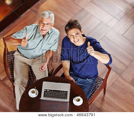 Man and senior in caf���© with laptop computer holding their thumbs up
