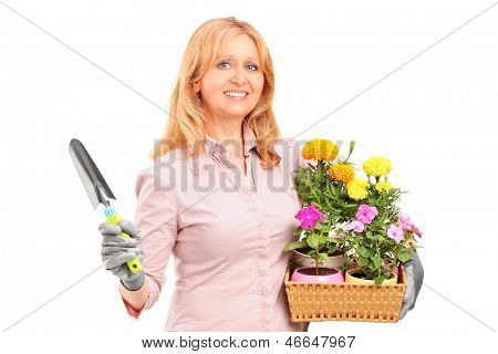 A female gardener holding flowers and gardening equipment isolated on white background