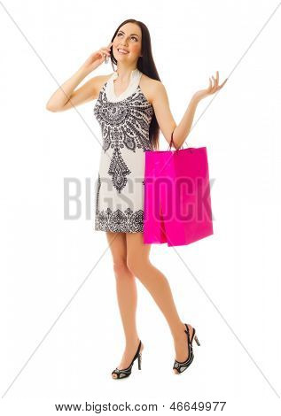 Young girl with paper bags talks by mobile phone isolated