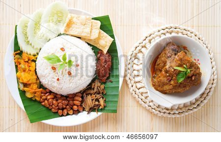 Nasi lemak is traditional malaysia spicy rice dish, fresh cooked with hot steam. Served with belacan, ikan bilis, acar, peanuts and cucumber. Decoration setup, malaysian cuisine.