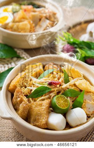 Hot and spicy Malaysian Curry Noodles or laksa  mee with hot steam in clay pot, decoration setup, serve with chopsticks. Malaysia cuisine.