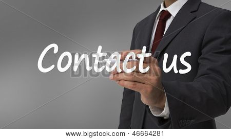 Businessman writing contact us with a marker against grey background