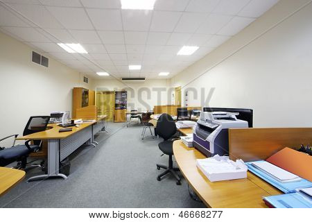 Empty working areas with armchairs and tables in light modern office.