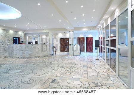 Reception area, glass entrance doors in office building at evening.