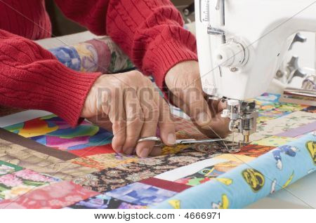 Quilter Cutting Thread On Sewing Machine.