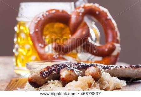 grilled sausages with sauerkraut and a pretzel poster
