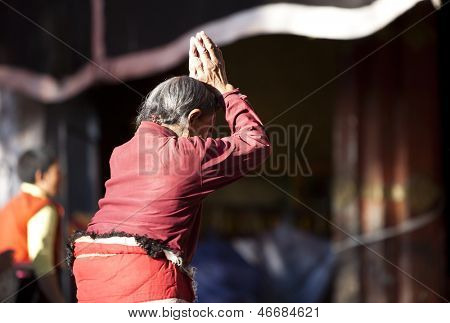 LHASA, TIBET-OCTOBER 08: An old female Tibetan buddhist pilgrim is praying in front of Jokhang Temple on October 08, 2011 in Lhasa, Tibet.
