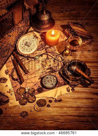 Ancient treasures border, pirates booty still life on wooden table, compass and map, golden coins and aged medallion, adventure concept