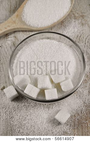 Refined white sugar in a bowl on a wooden table