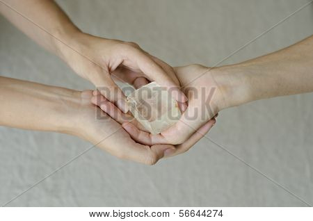 Womans Hands Giving A Quartz Crystal One To Another