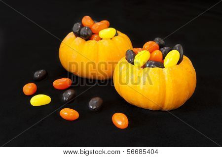 Mini pumpkins filled with Halloween jellybeans on a black background poster