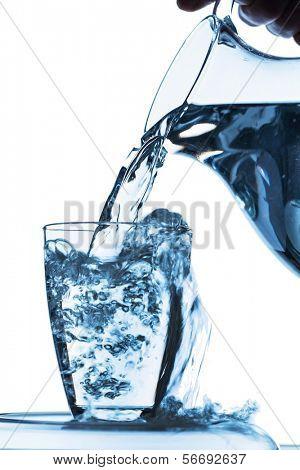 água pura é esvaziada em um copo de água de um jarro. água potável