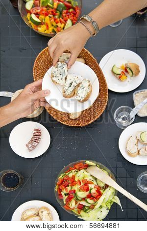 Summer Styled dinner table, with one hand passing a plate with bread and French Blue Cheese to another dinner guest, seen from above
