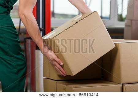 Hands Of Warehouse Worker Lifting Box