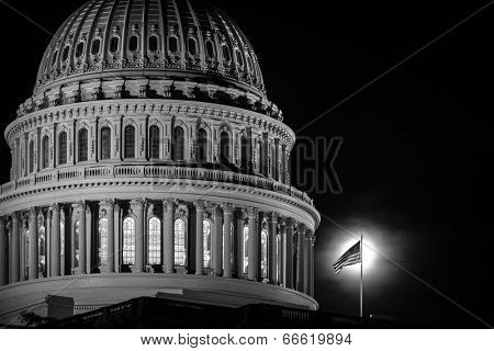 The Capitol dome and U.S. National flag with moonlight backlit.