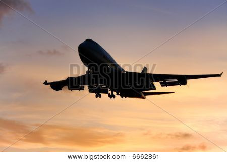 Silhouette of jumbo jet airliner at sunset.