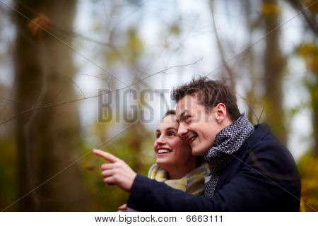 Cute Young Couple Looking And Ppointing Up At Something