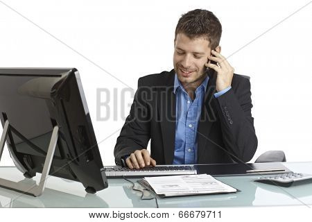 Young businessman sitting at desk, talking on mobilephone, typing on keyboard, smiling.