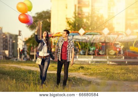 Affectionate couple walking together in the amusement park poster