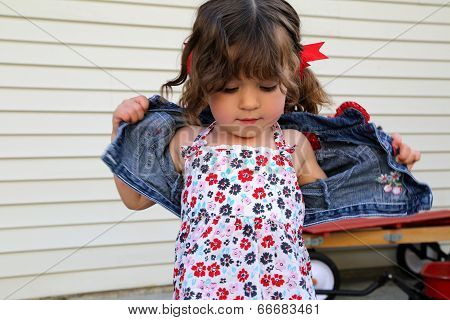 Little Girl Taking Off Coat