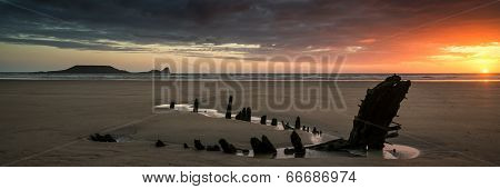 Landscape Panorama Ship Wreck On Rhosilli Bay Beach In Wales At Sunset