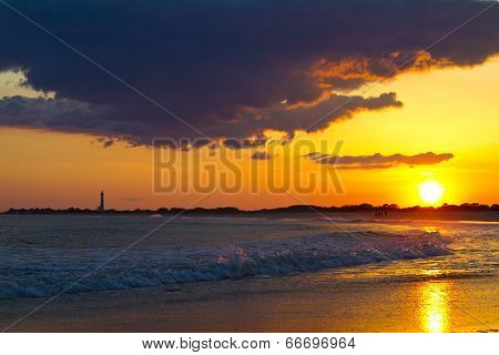 Sunset Over The Cape May New Jersey Shore With The Lighthouse In The Distance