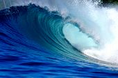 Blue surfing wave breaking on tropical island reef poster